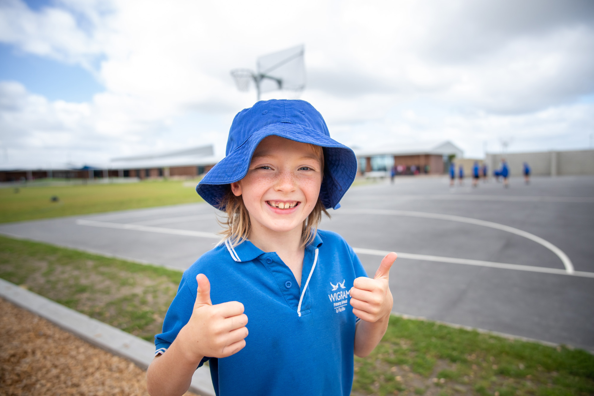 Wigram Primary female student in blue bucket hat showing two thumbs up with playground in the background