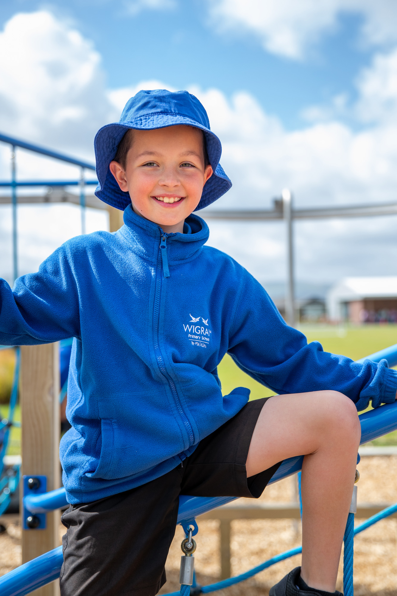young male wearing blue and blue bucket hat on a climbing fame on an outdoor playground