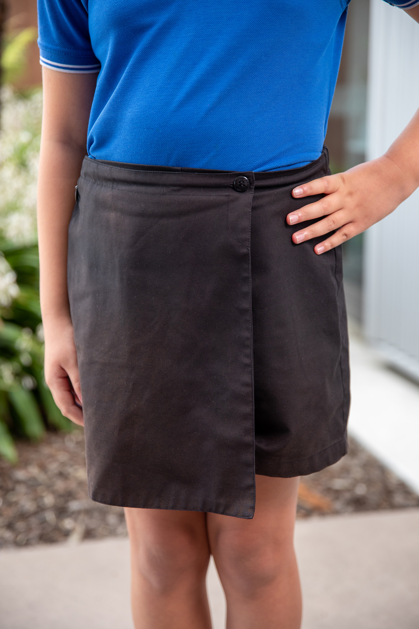 female Wigram Primary pupil wearing black skorts with arm on her hip