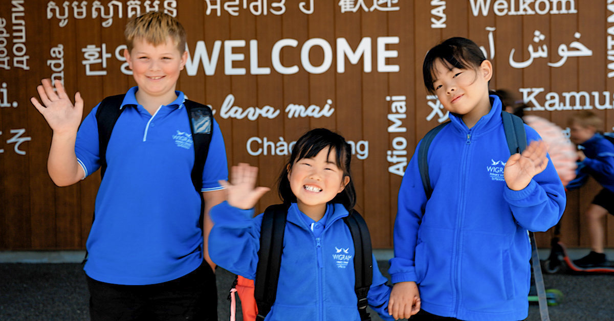 Three Wigram Primary students in blue wearing backpacks and waving