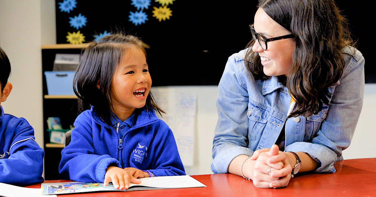 female teacher smiling at Wigram Primary pupil wearing blue with an open book in front of her