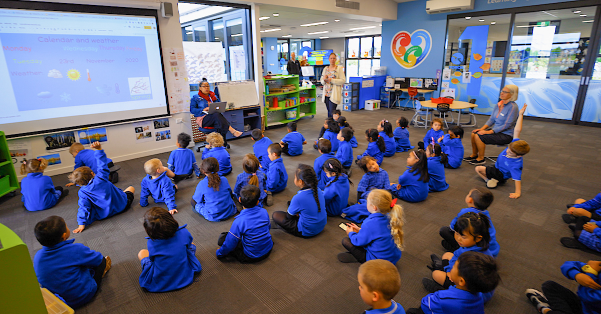 wigram primary students in blue seated on the floor of a classroom with three teachers and looking at a projector screen