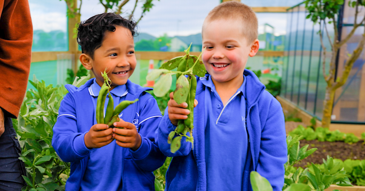 two young male students in blue holding up green beans in a vegetable garden