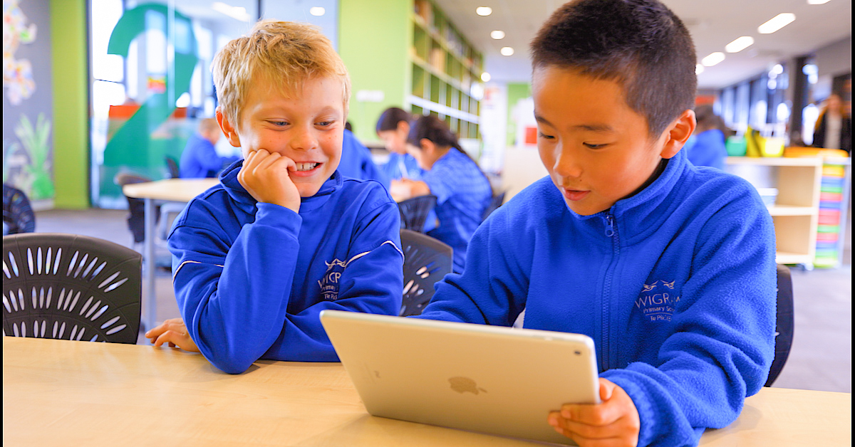 two young male students in blue fleeces at a desk sharing an ipdad