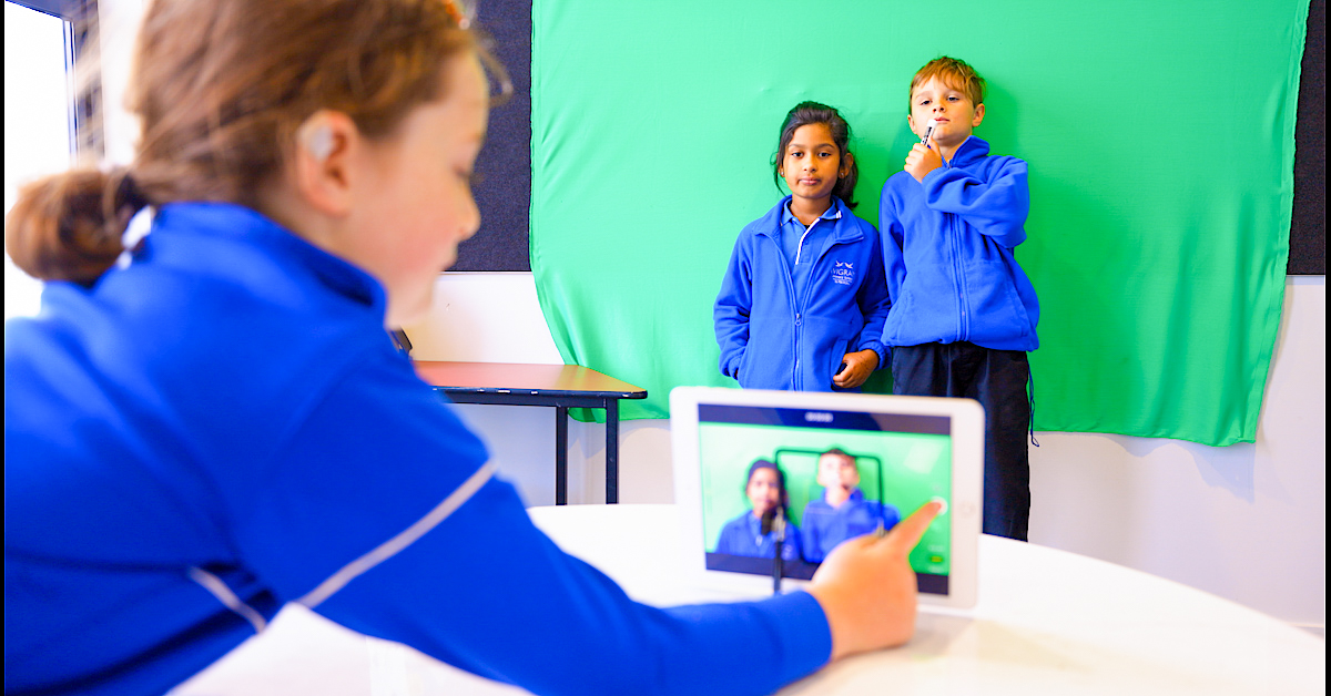 female pupil in blue taking a video of two pupils also in blue standing against a green background