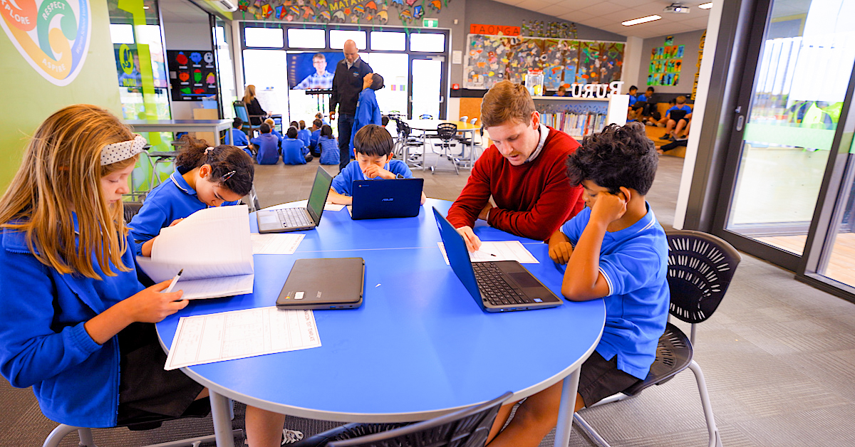 male teacher in red jersey seated at a round blue desk with four pupils on laptops
