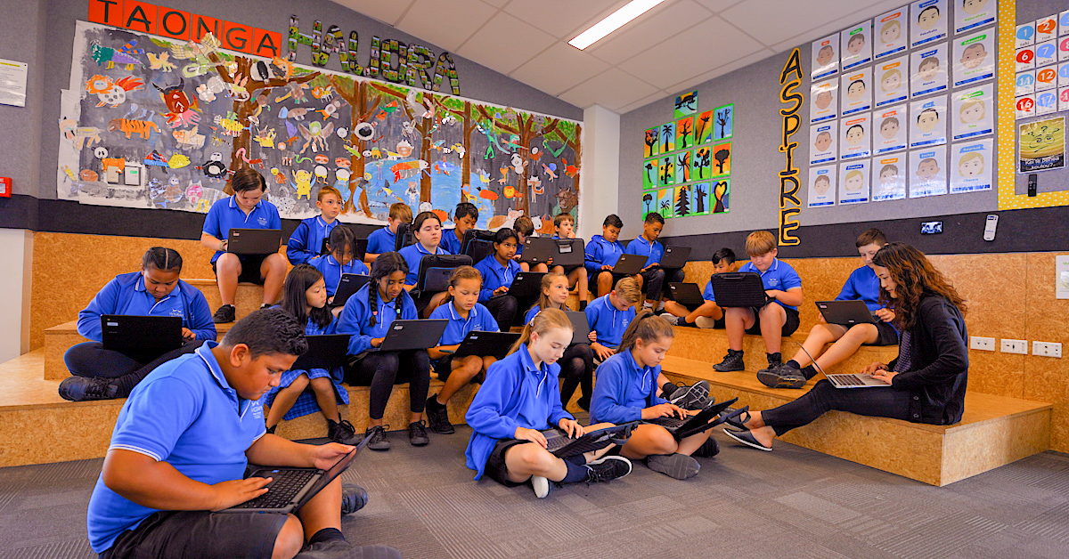wigram primary students seated on a stadium seat in their classroom with laptops on their laps