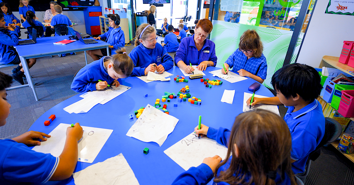 Wigram Primary pupils seated at a round blue table all with white paper and green pens